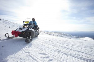 people on snowmobile in winter mountain